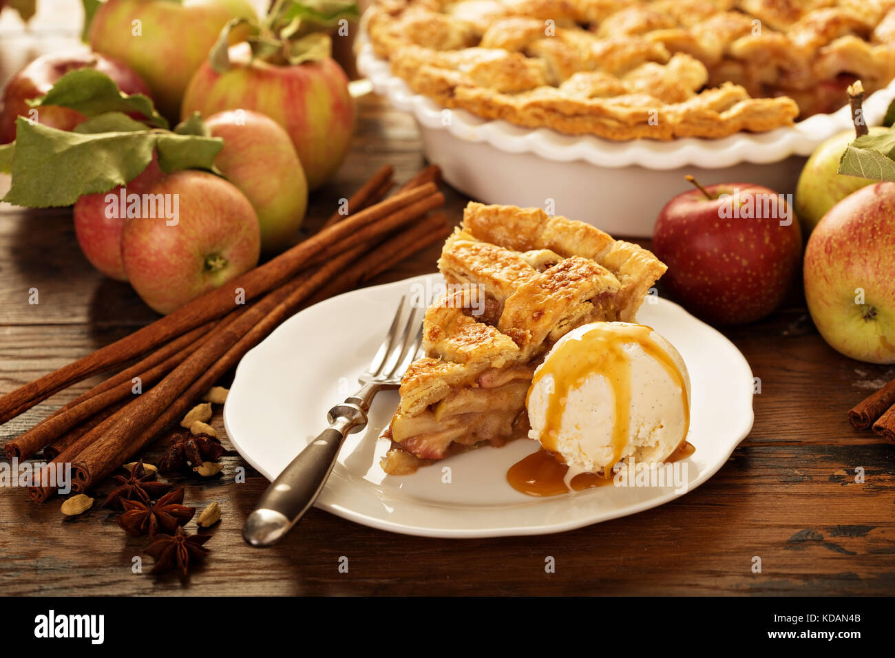 Piece of an apple pie with ice cream on a plate - Stock Image