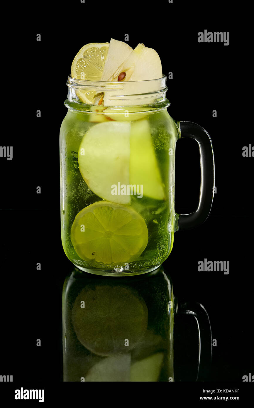 Cocktail with lemon, apple and pistachios syrup in jar on black background with reflection - Stock Image