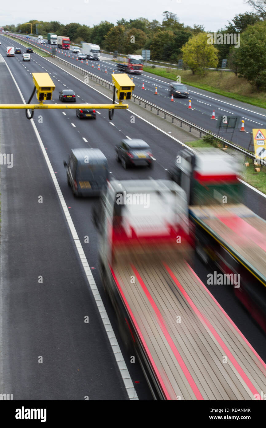 Bright yellow speed cameras in an average speed check area with moving traffic flowing through a roadworks area - Stock Image