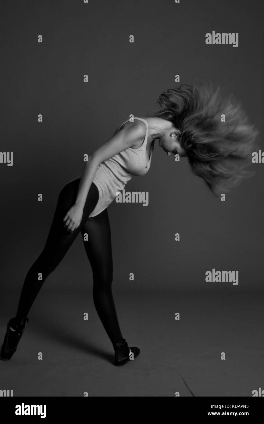 young beautiful woman dancer with long black hair wearing gray vest and tights jumping on a light gray studio background - Stock Image