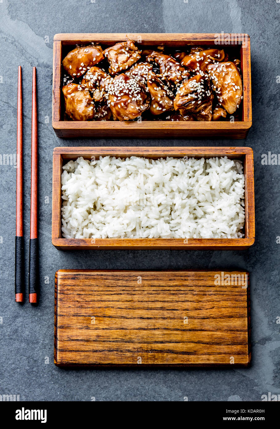 Japanese food chicken teriyaki with rice in wooden bento lunch box japanese food chicken teriyaki with rice in wooden bento lunch box slate background top view forumfinder Gallery
