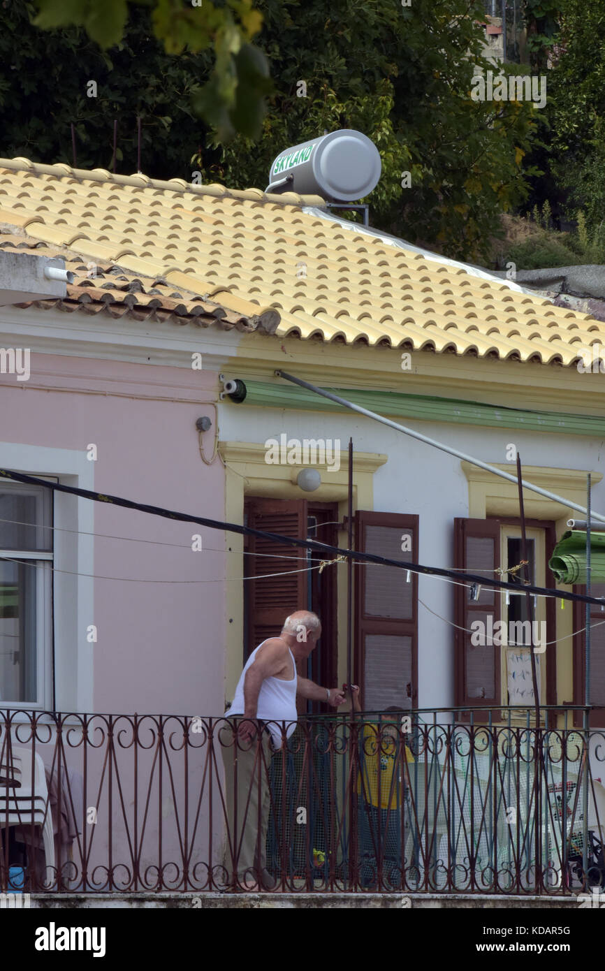 an elderly gentleman on the balcony of his apartment or flat wearing a white vest in kassiopi, corfu, Greece. - Stock Image