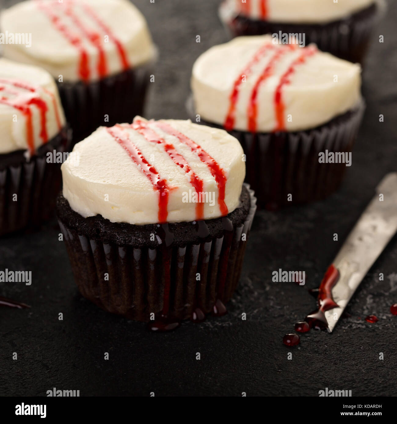 Spooky Halloween themed cupcakes with fake blood - Stock Image