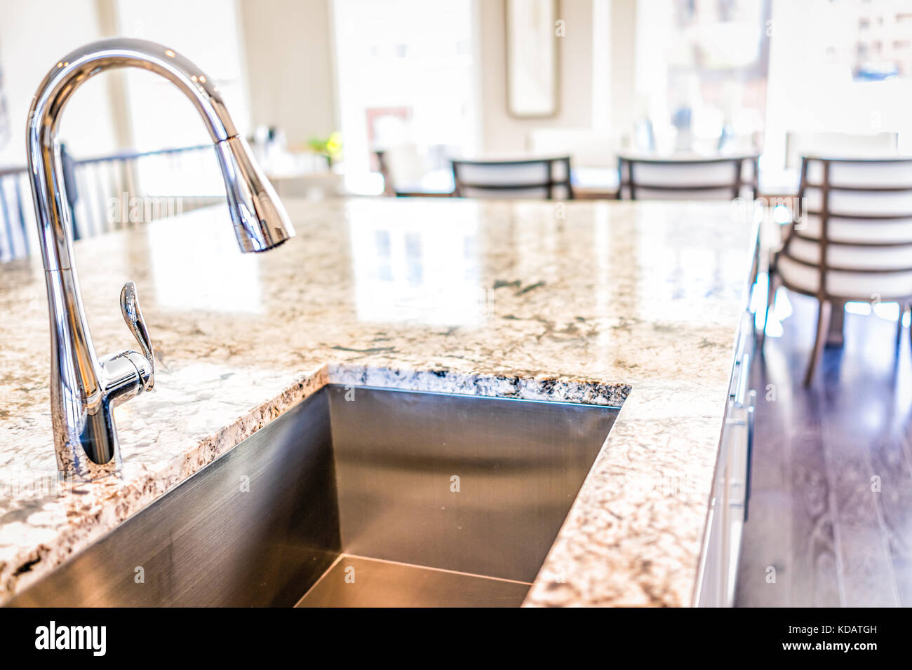 New modern faucet and kitchen room sink closeup with island and