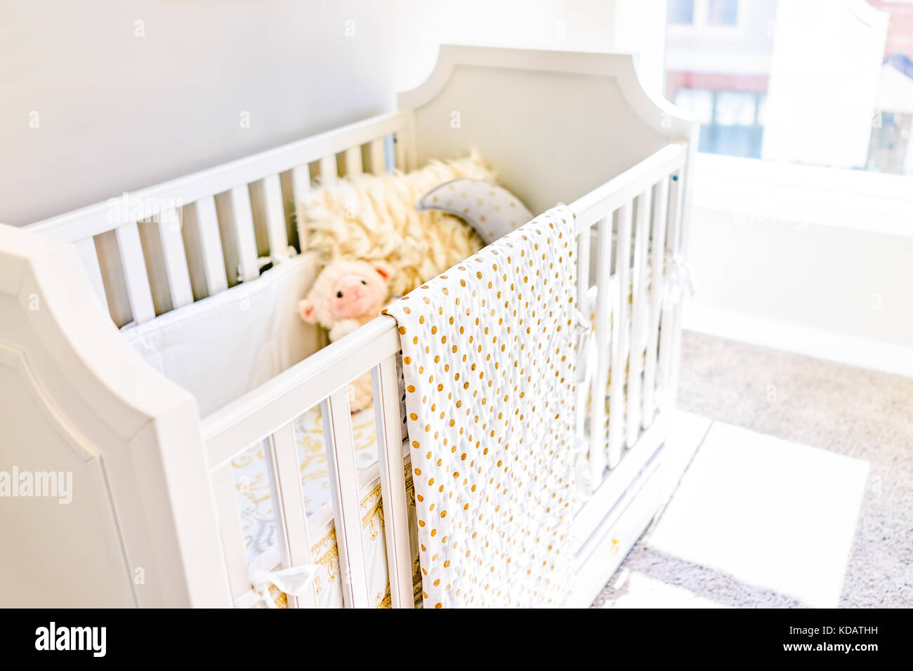 Closeup of bright yellow baby crib in nursery room with toys and pillow in model staging home, apartment or house - Stock Image