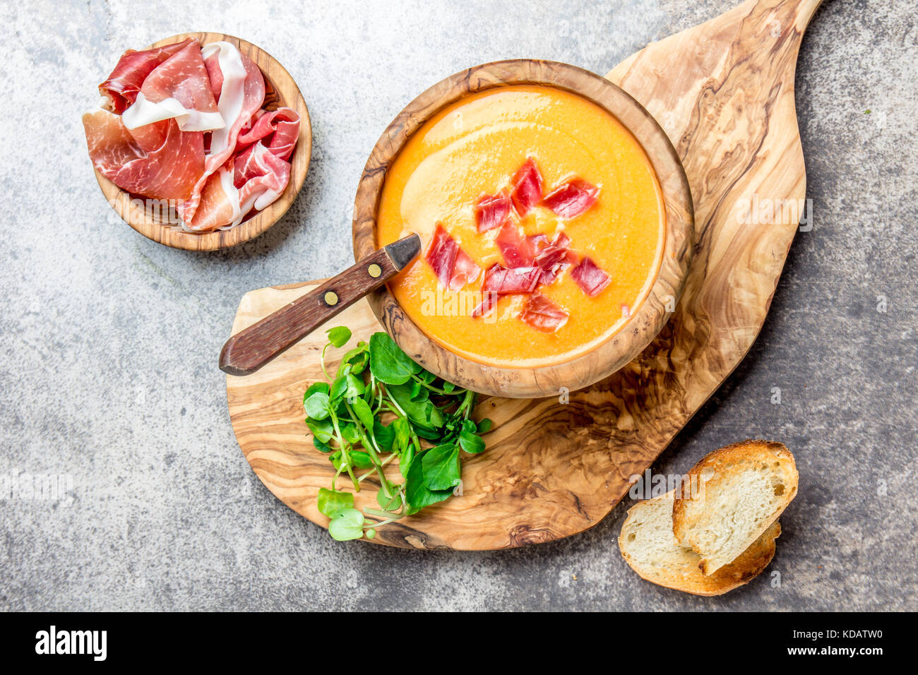 Spanish tomato soup Salmorejo served in olive wooden bowl with ham jamon serrano on stone background. Top view. Stock Photo