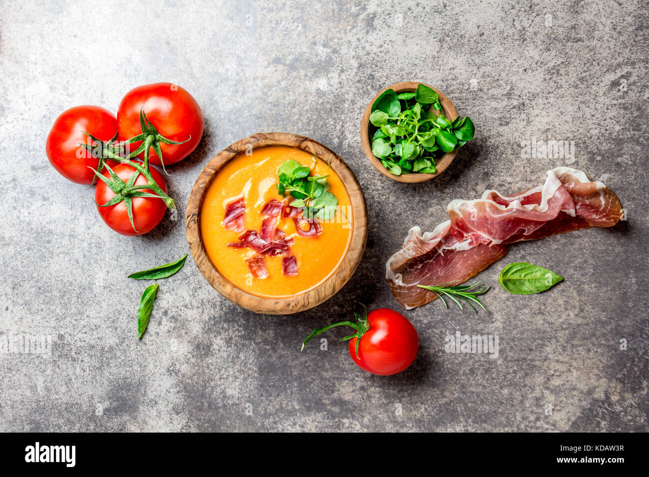 Spanish tomato soup Salmorejo served in olive wooden bowl with ham jamon serrano on stone background. Top view. - Stock Image