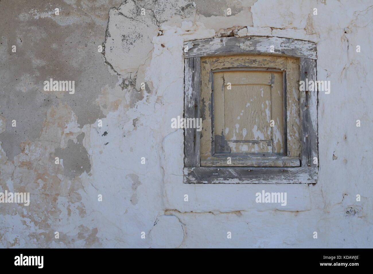 verwittertes geschlossenes Fenster an einer bröckelnden Haus Fasade - weathered closed window on a crumbling - Stock Image