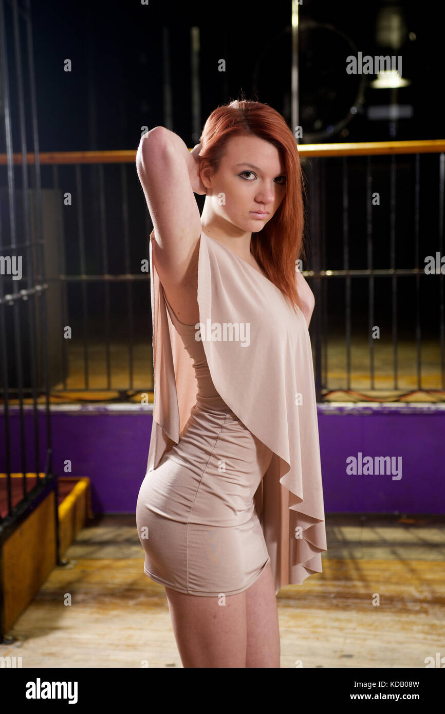Pretty girl wearing a mini-dress in a night club location - Stock Image