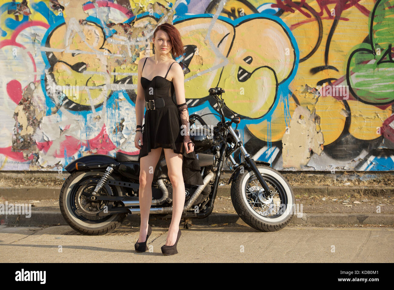 Pretty girl in a short black dress and high heels with a motorcycle against a graffiti background - Stock Image