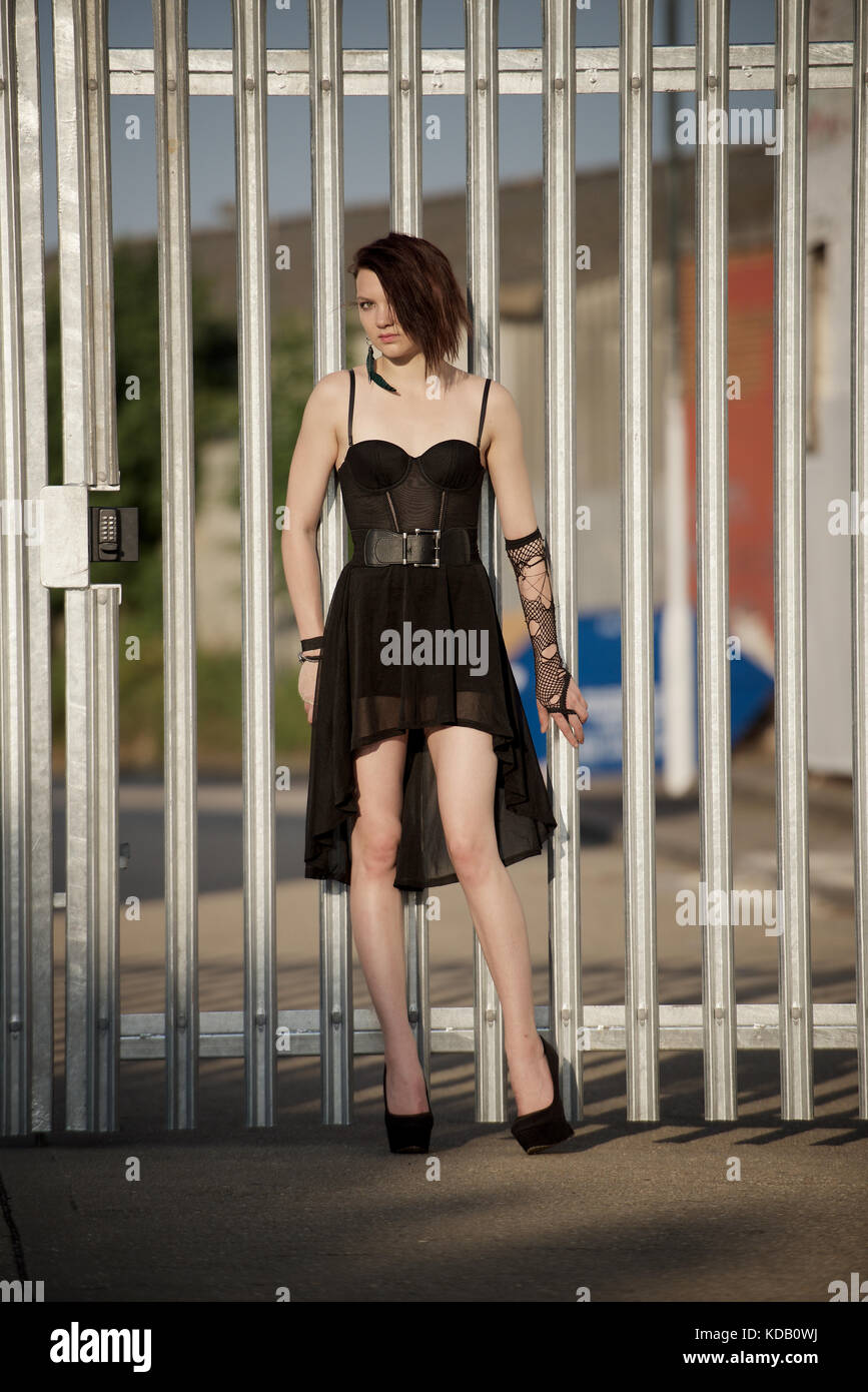 Girl in short black dress and high heels outdoors - Stock Image