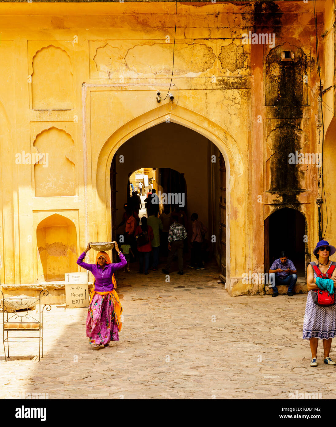 An India woman carrying a pan on her head at a palace building in Jaipur, India - Stock Image