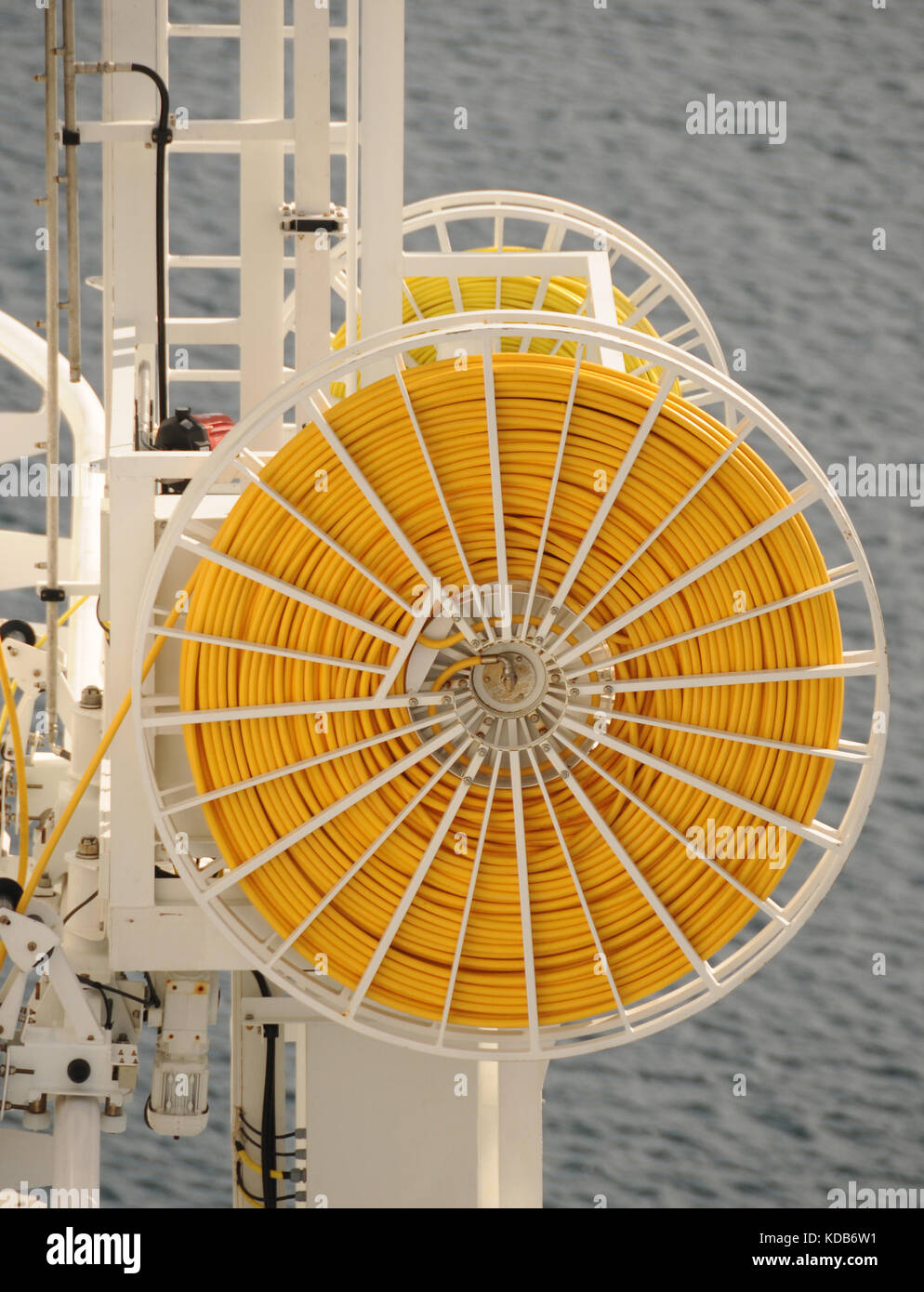 Ship side fire hose in yellow color - Stock Image