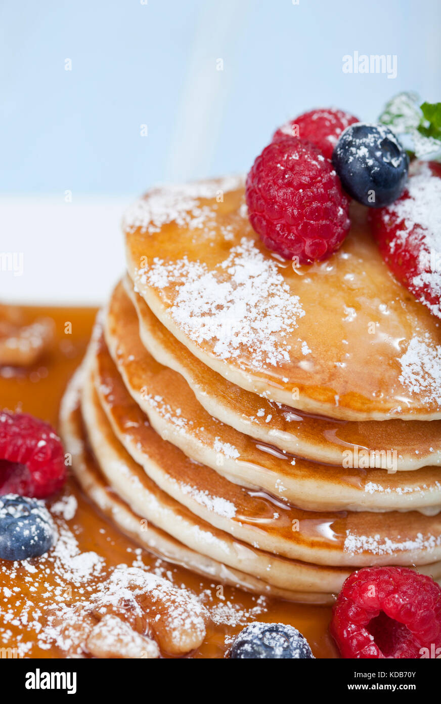 Stack of pancakes with mixed berries and maple syrup - Stock Image