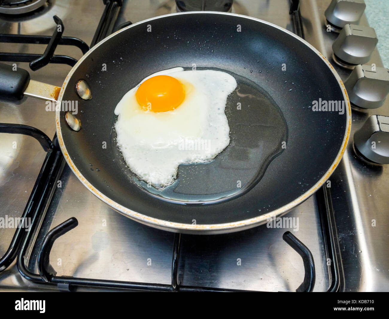 An egg being fried in sunflower oil in a small Teflon coated non stick frying pan on a gas hob - Stock Image