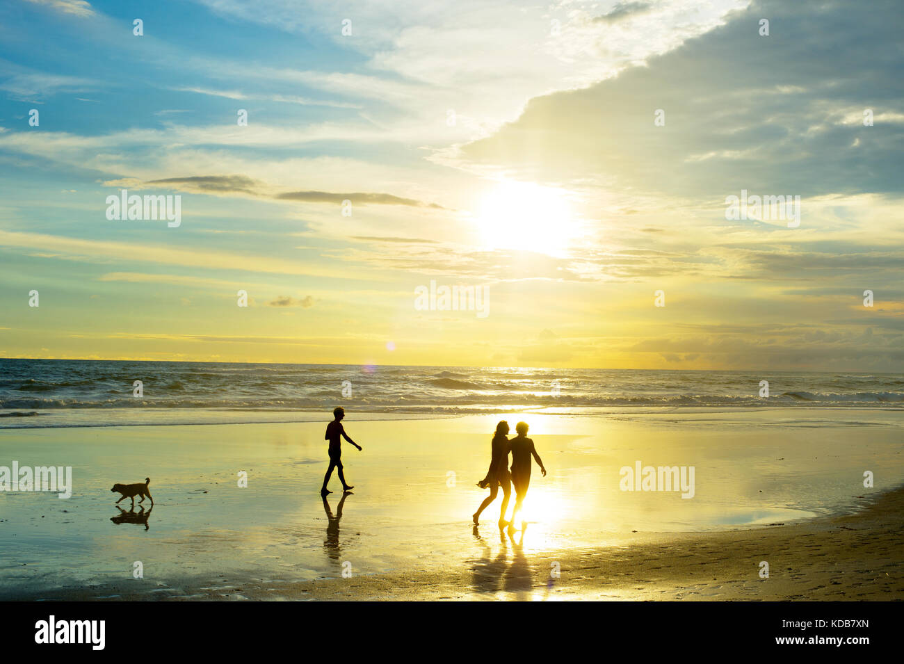 People walking on tropical Bali ocean beach at sunset. Indonesia Stock Photo