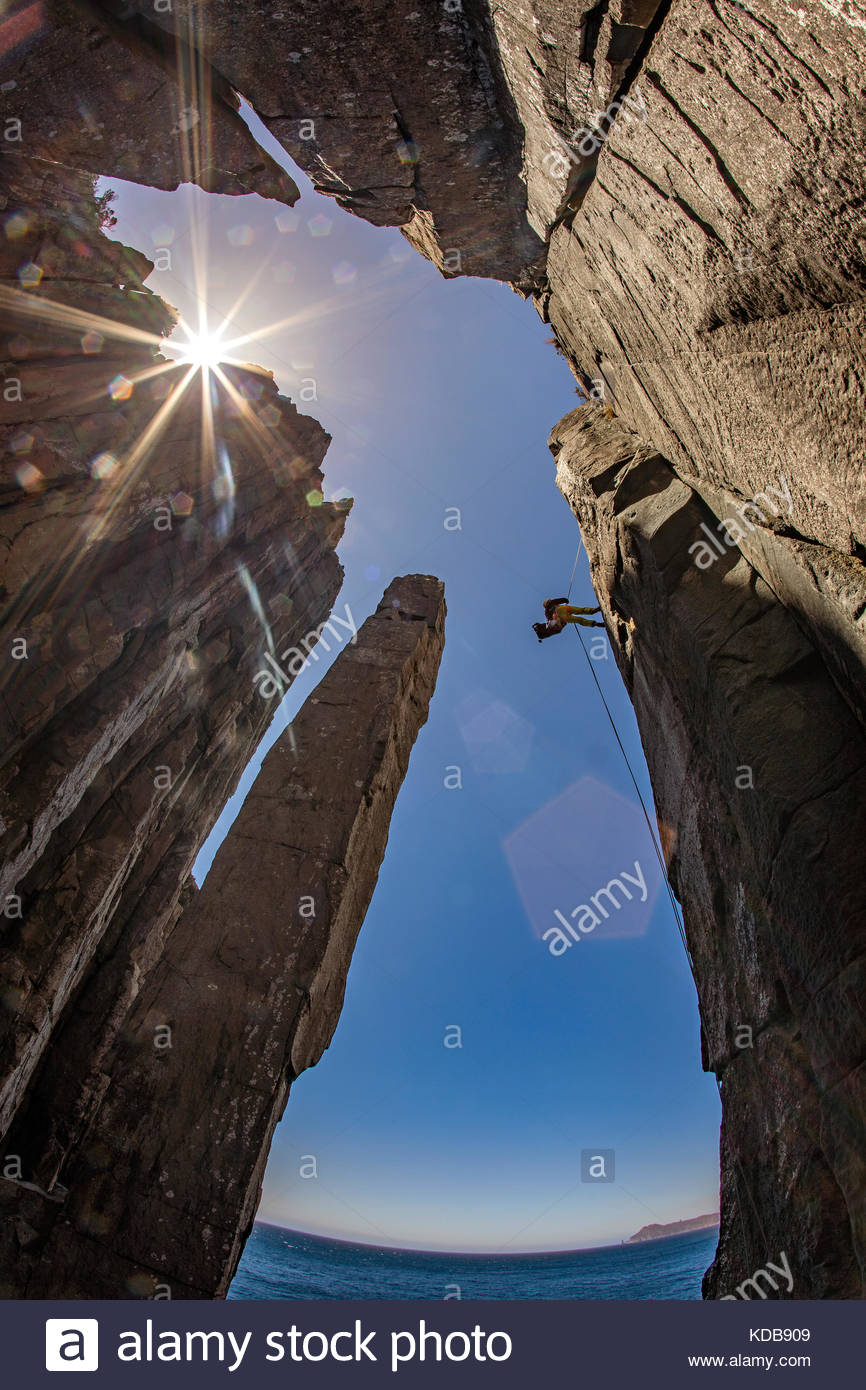 A climber abseils down to the base of the Totem Pole, where the climb begins. - Stock Image