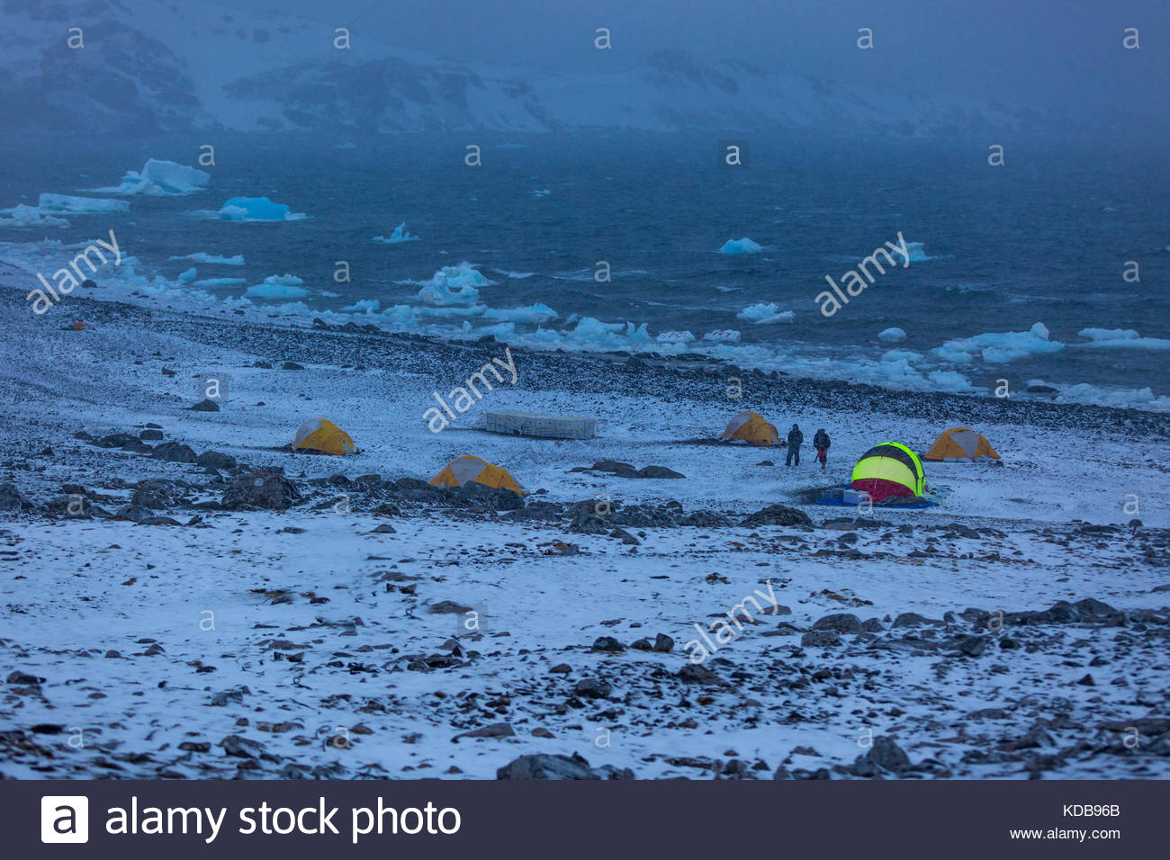 Two researchers walking near camp in Antarctica. - Stock Image