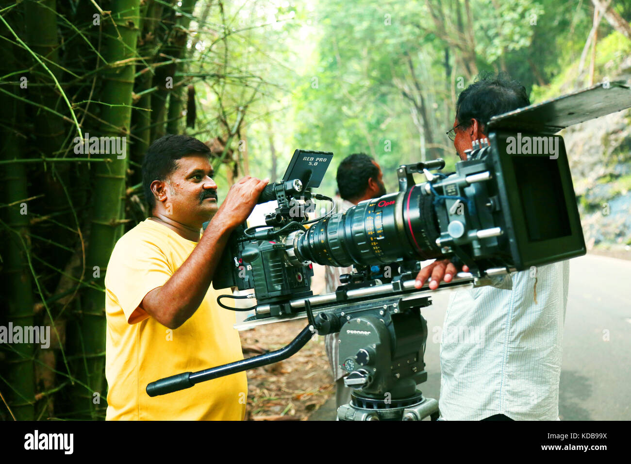 Video camera operator on nature background, film shooting spot - Stock Image