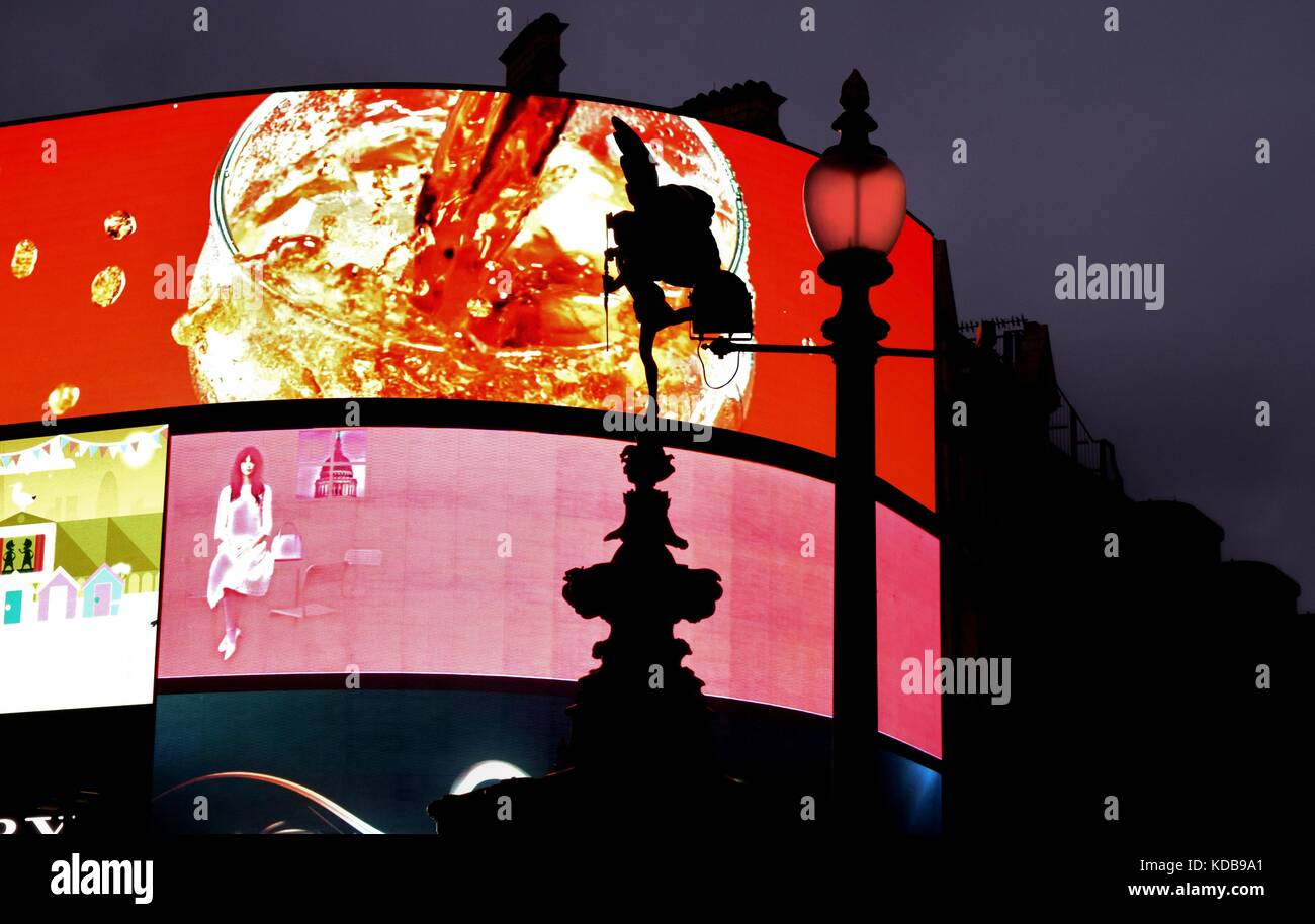 Digital commercial / marketing / advertising screens lit up in Piccadilly Circus London, with a silhouette of the - Stock Image