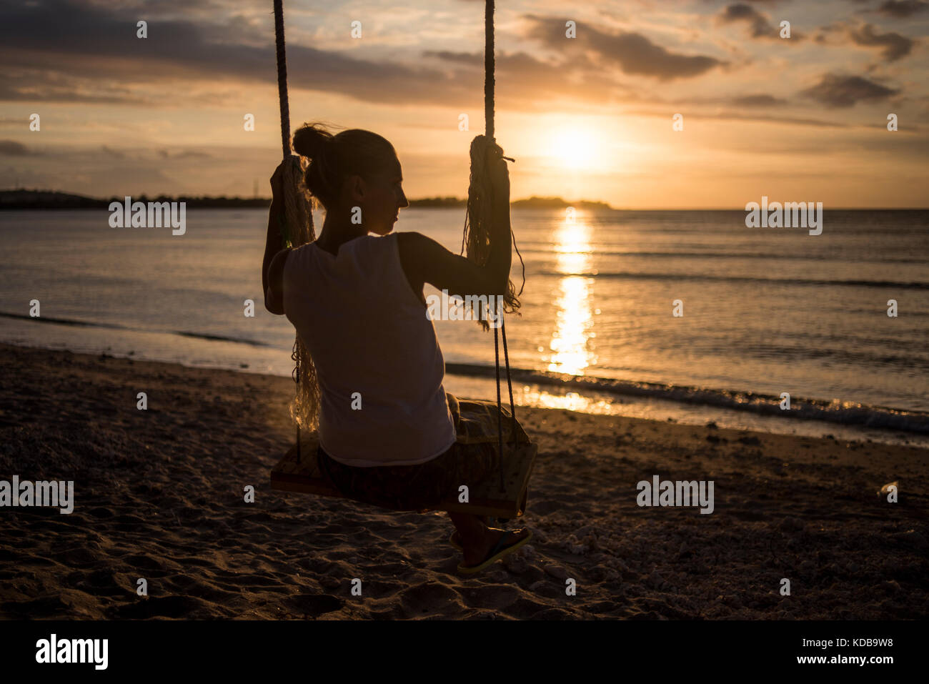 A silhouette of a young woman on a swing in a beach of Gili Air, Gili Islands, Indonesia. - Stock Image