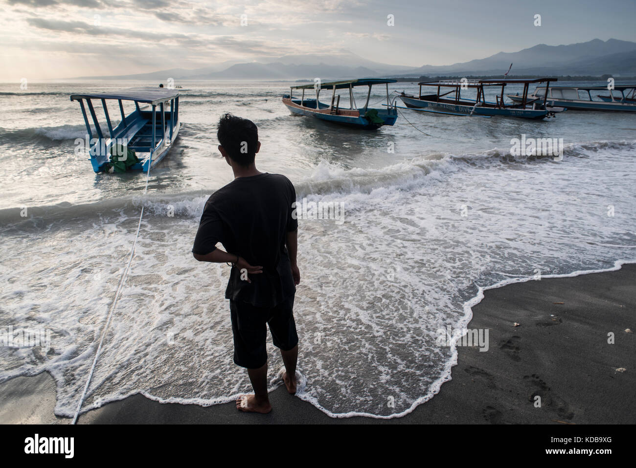 A local men checks his wooden boats during bad weather in Gili Air, Gili Islands, Indonesia. - Stock Image