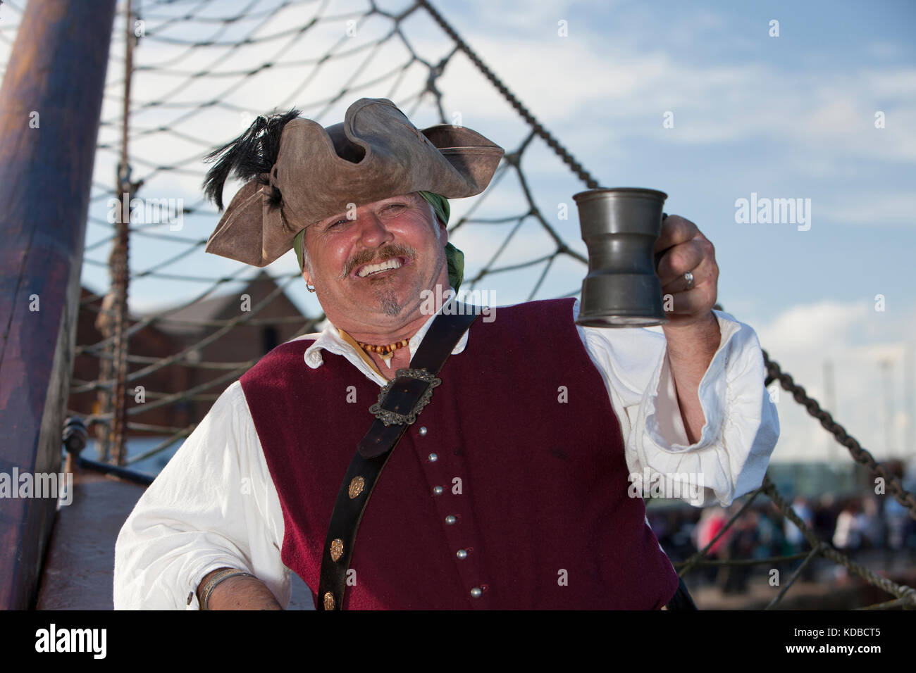 Jolly pirate 'Captain Andreas' holding tankard aboard the Albatross in Wells harbour. - Stock Image