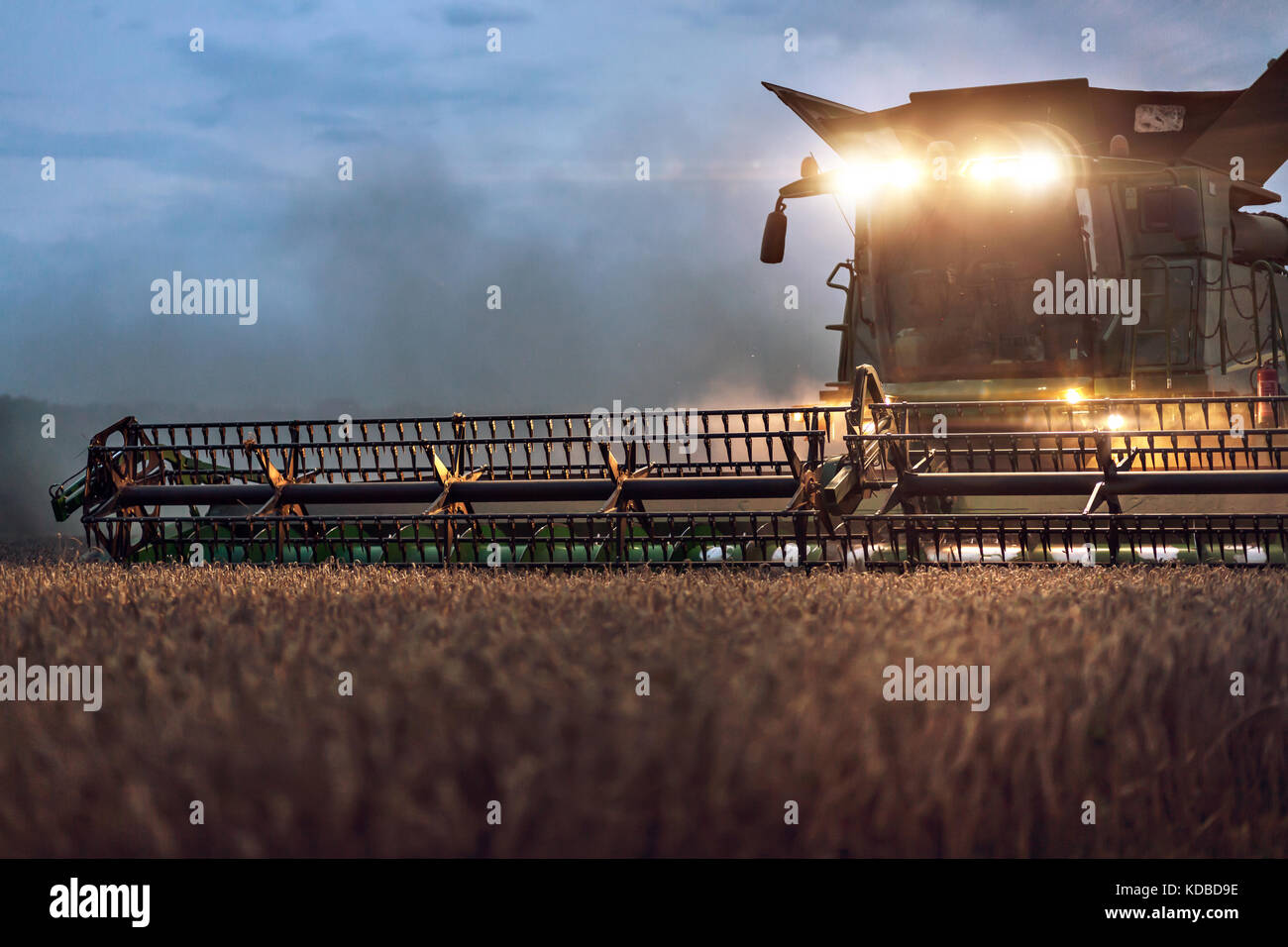 Partial view of a combine on a field at night - Stock Image