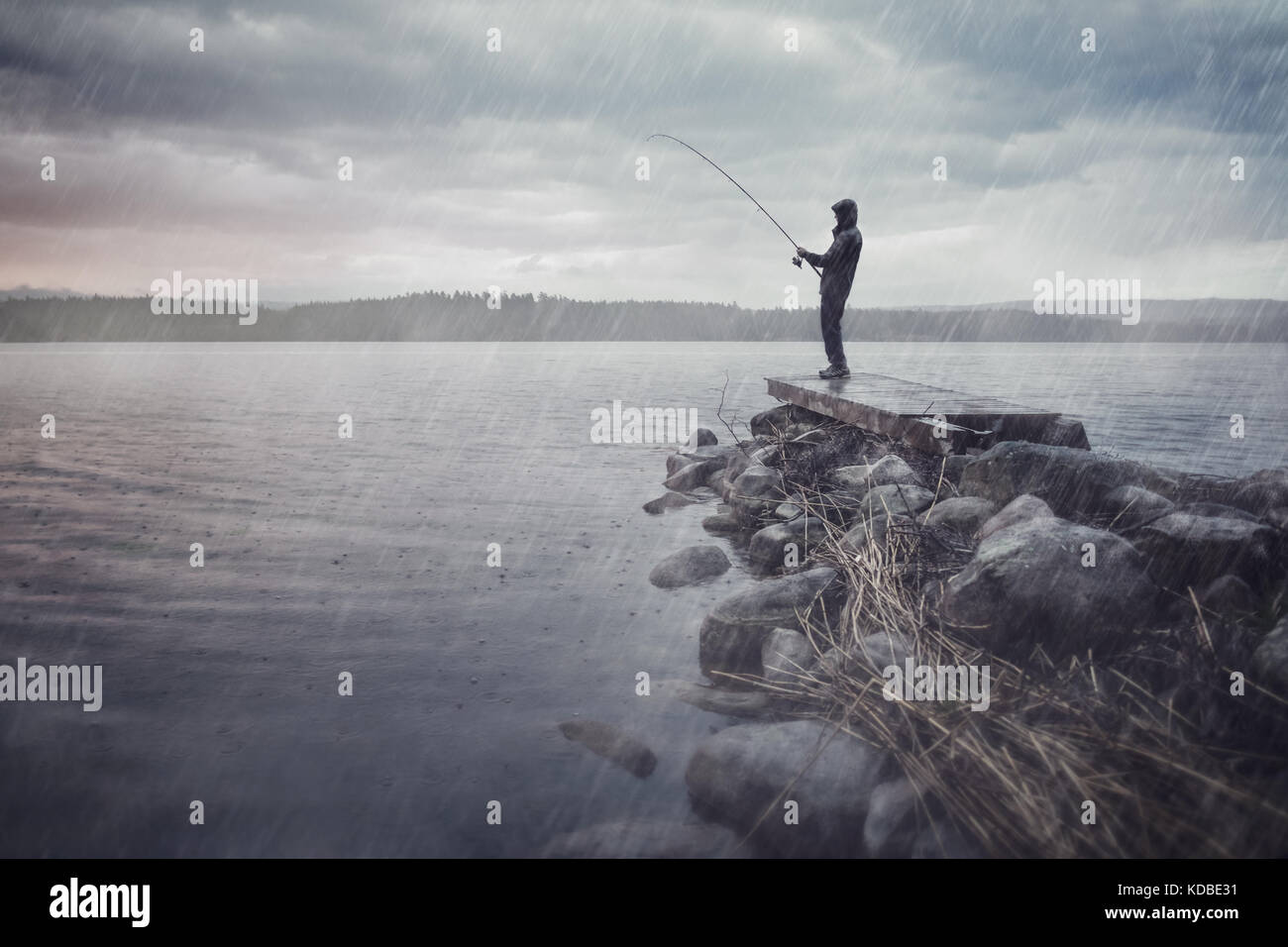 Man at a lake fishing in the rain - Stock Image