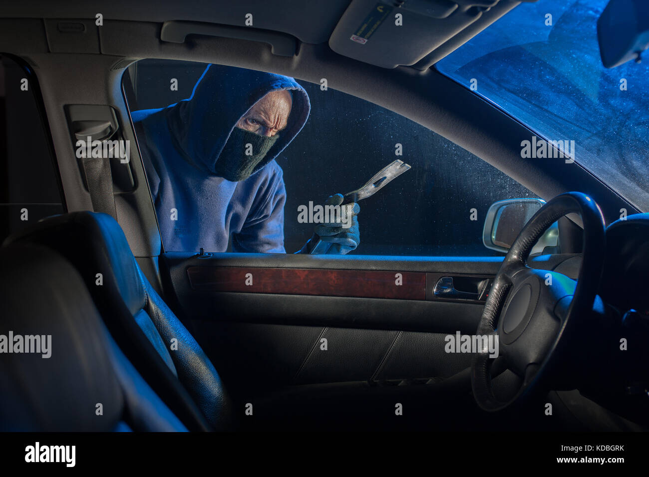 Car thief breaking into a car at night - Stock Image