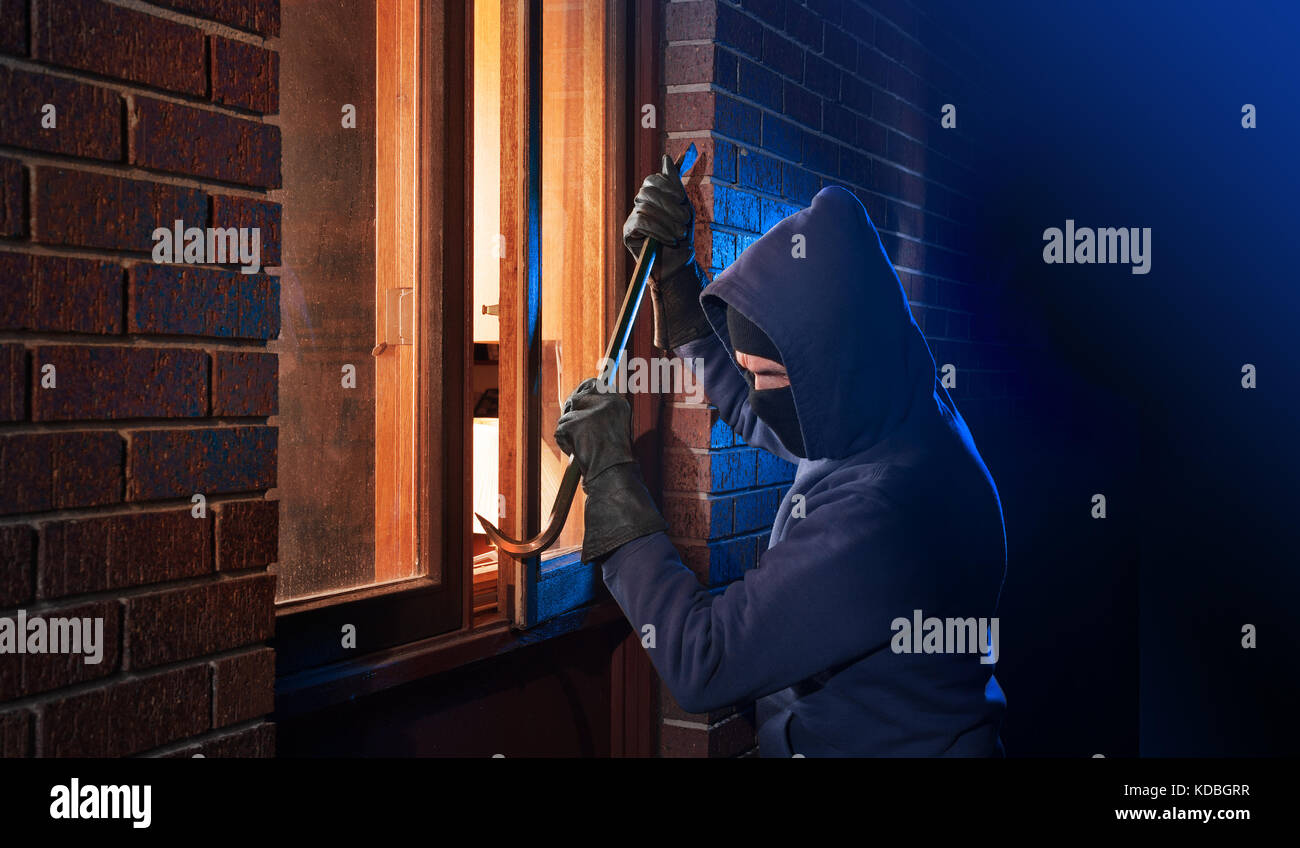 Hooded burglar breaking into a house - Stock Image