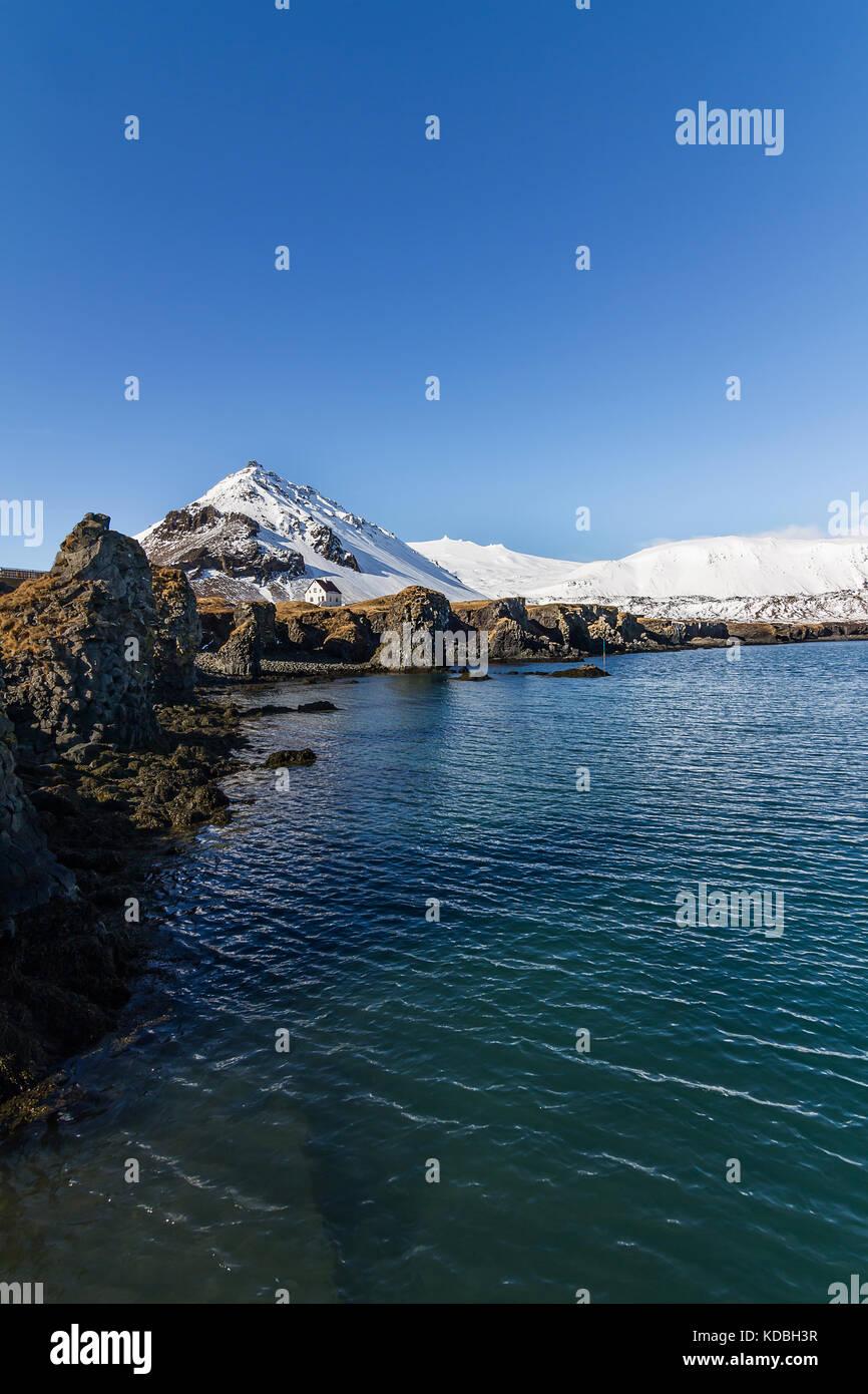 Arnarstapi harbor with Volcano glacier Snaefellsjokull in the background - Stock Image