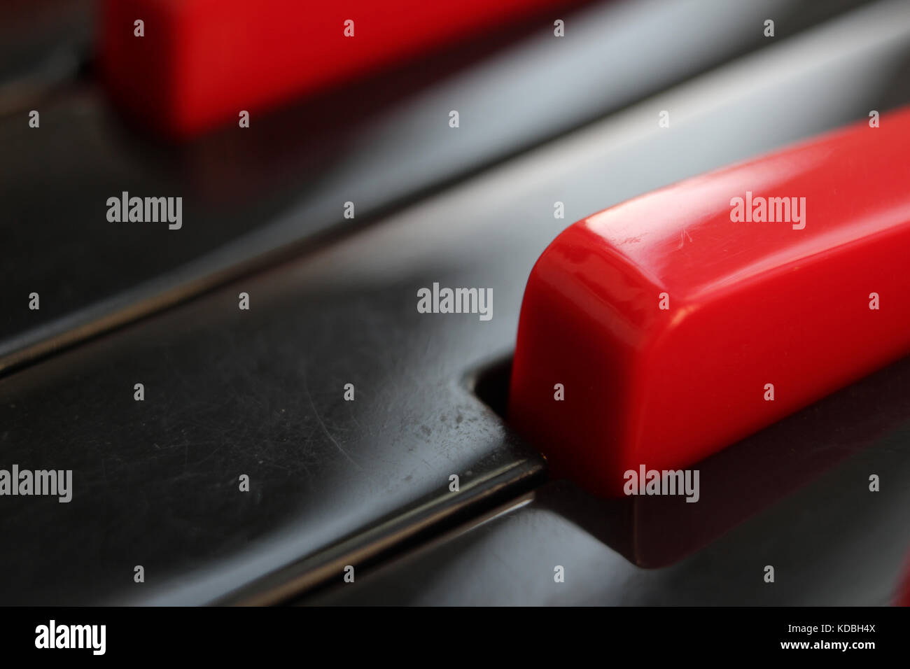 Closeup of black and red keys of melodica keyboard. - Stock Image