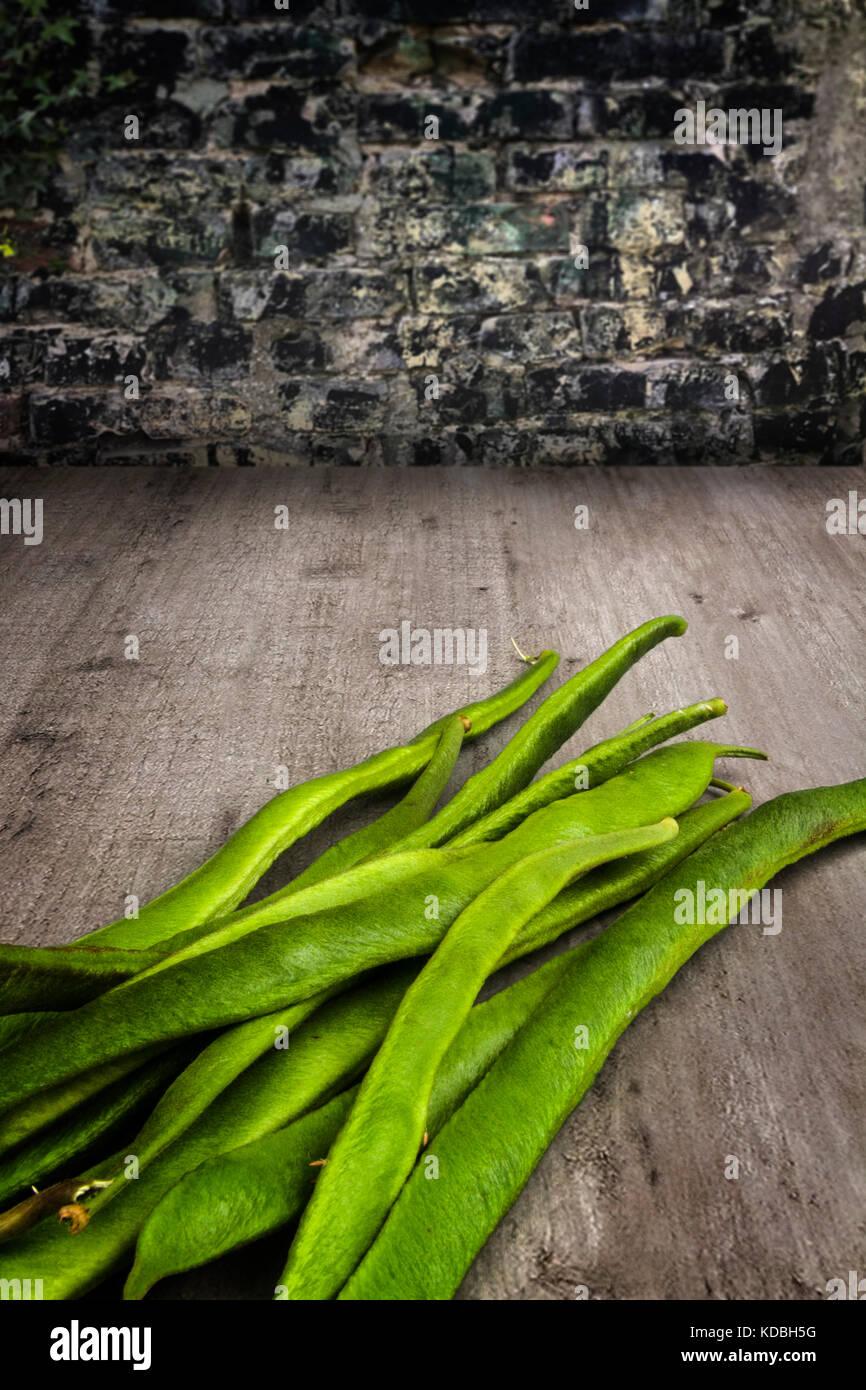 Fresh runner beans on a wooden table - Stock Image