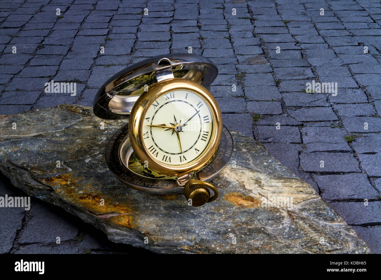 Traditional travelling clock on a piece of slate on a cobblestone pavement - Stock Image