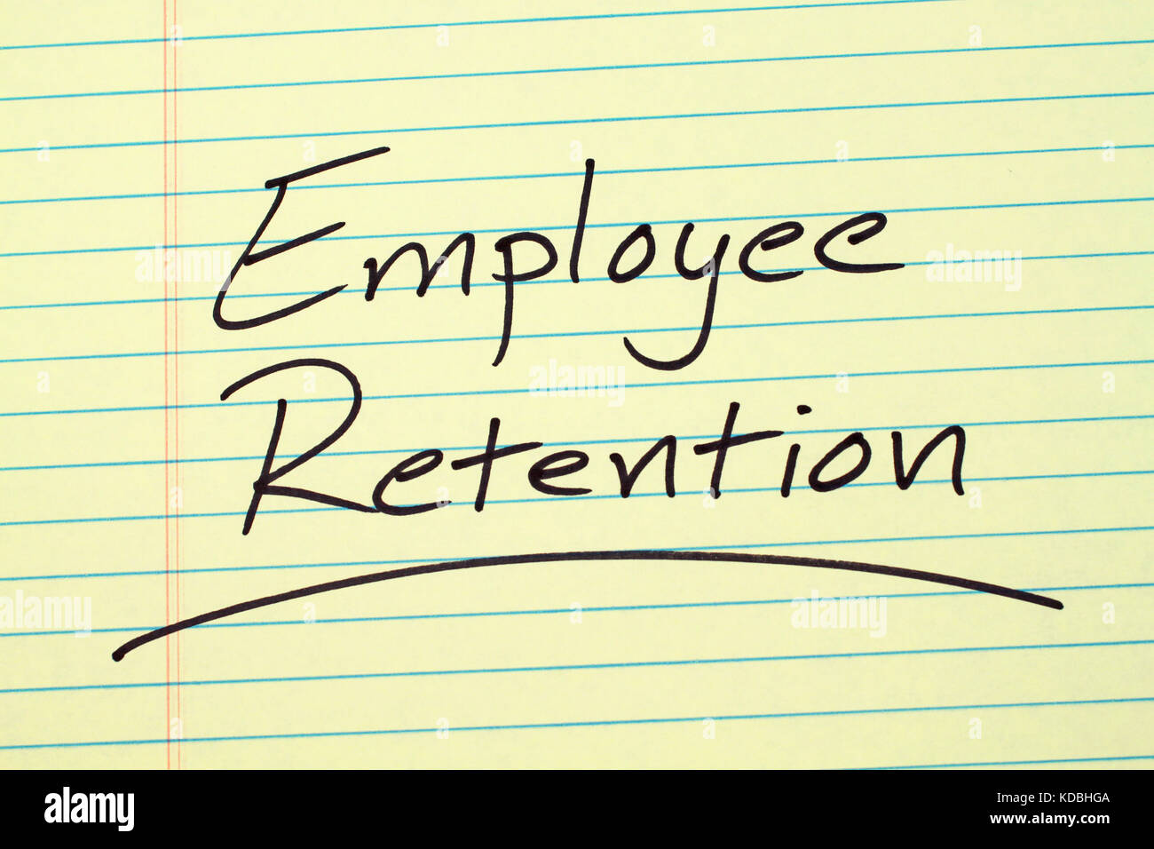The word 'Employee Retention' underlined on a yellow legal pad - Stock Image