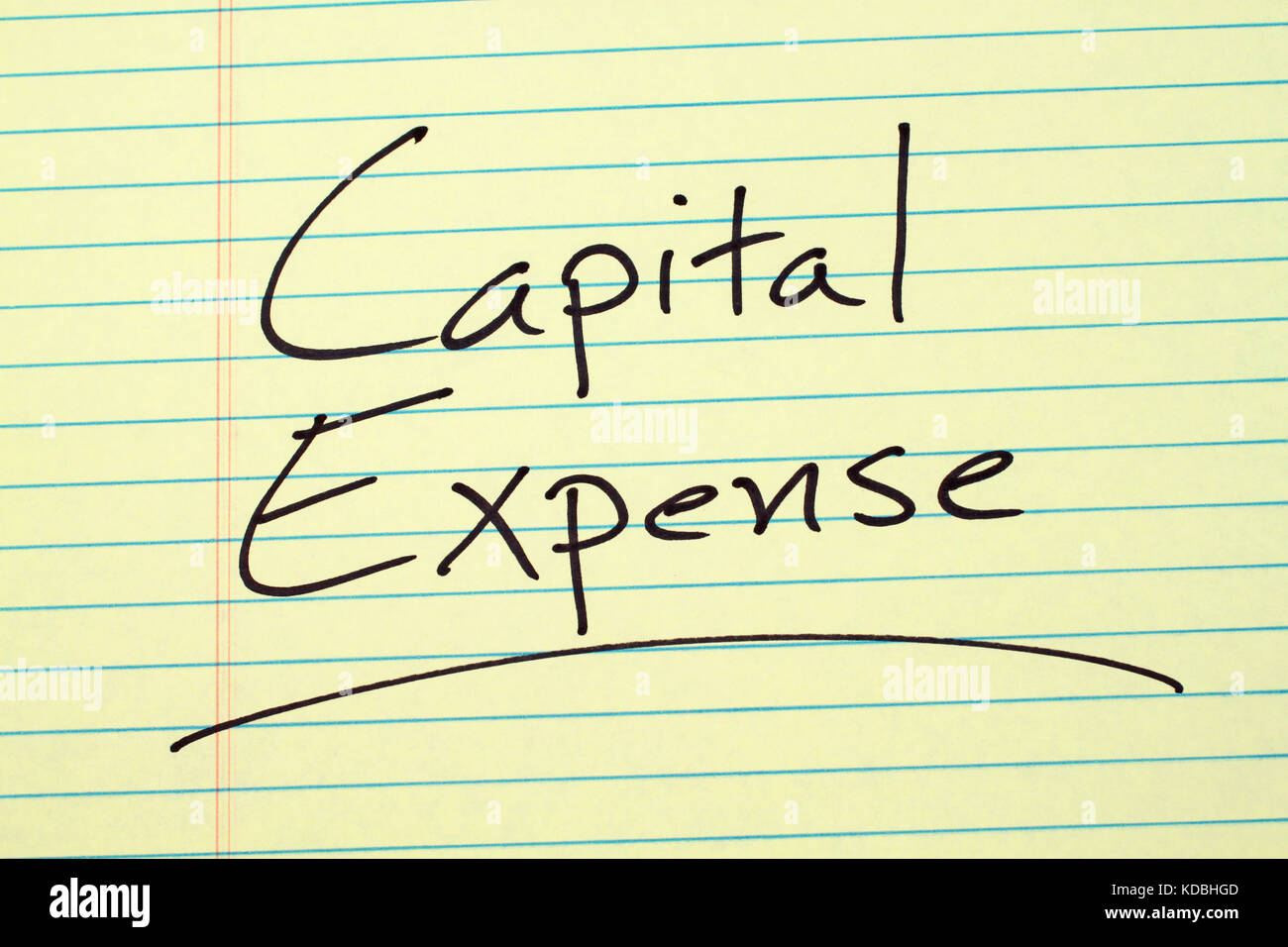 "The word ""Capital Expense"" underlined on a yellow legal pad Stock Photo"
