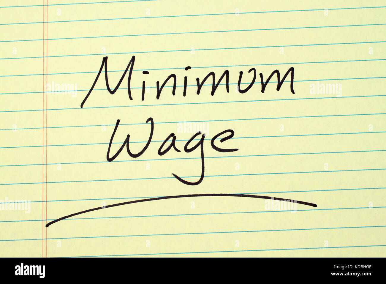 The word 'Minimum Wage' underlined on a yellow legal pad - Stock Image