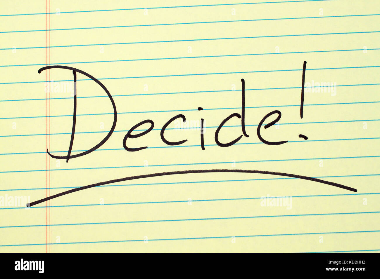The word 'Decide!' underlined on a yellow legal pad - Stock Image