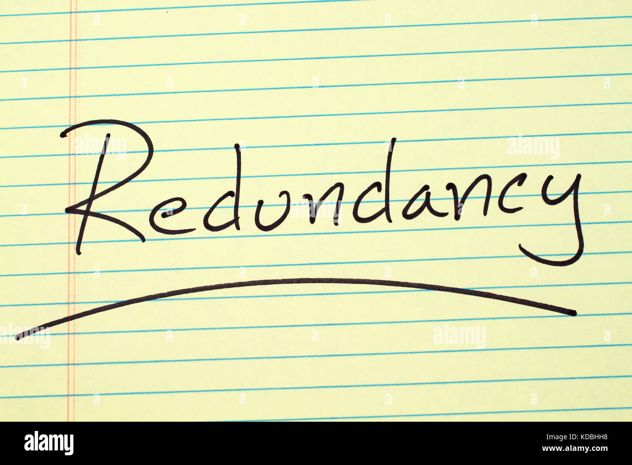 The word 'Redundancy' underlined on a yellow legal pad - Stock Image
