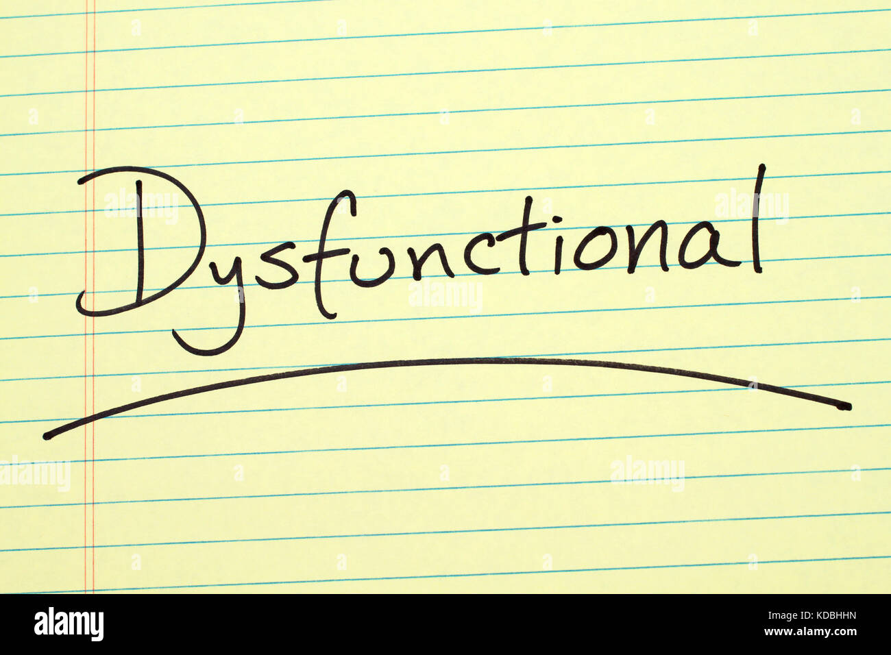 The word 'Dysfunctional' underlined on a yellow legal pad - Stock Image