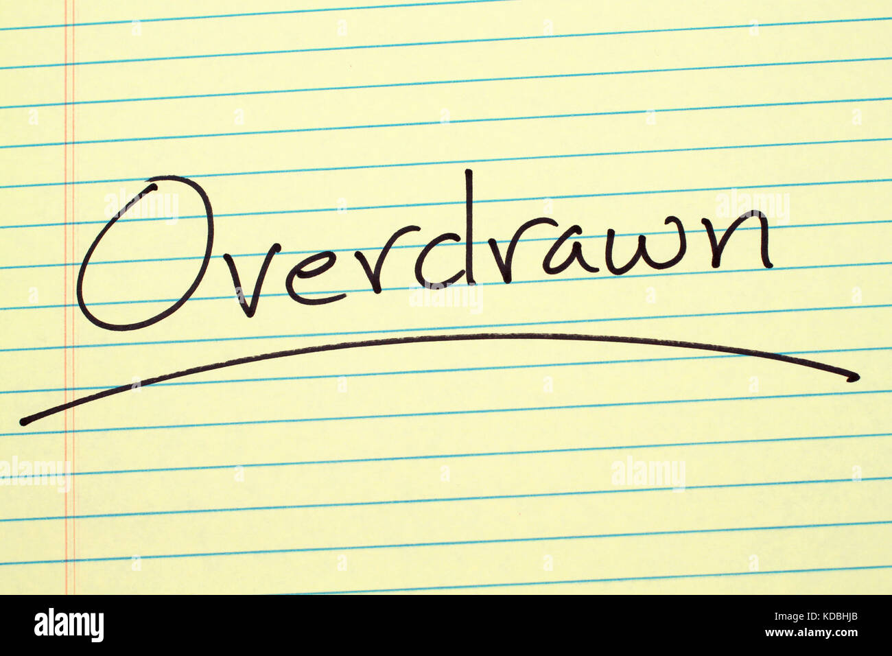 The word 'Overdrawn' underlined on a yellow legal pad - Stock Image