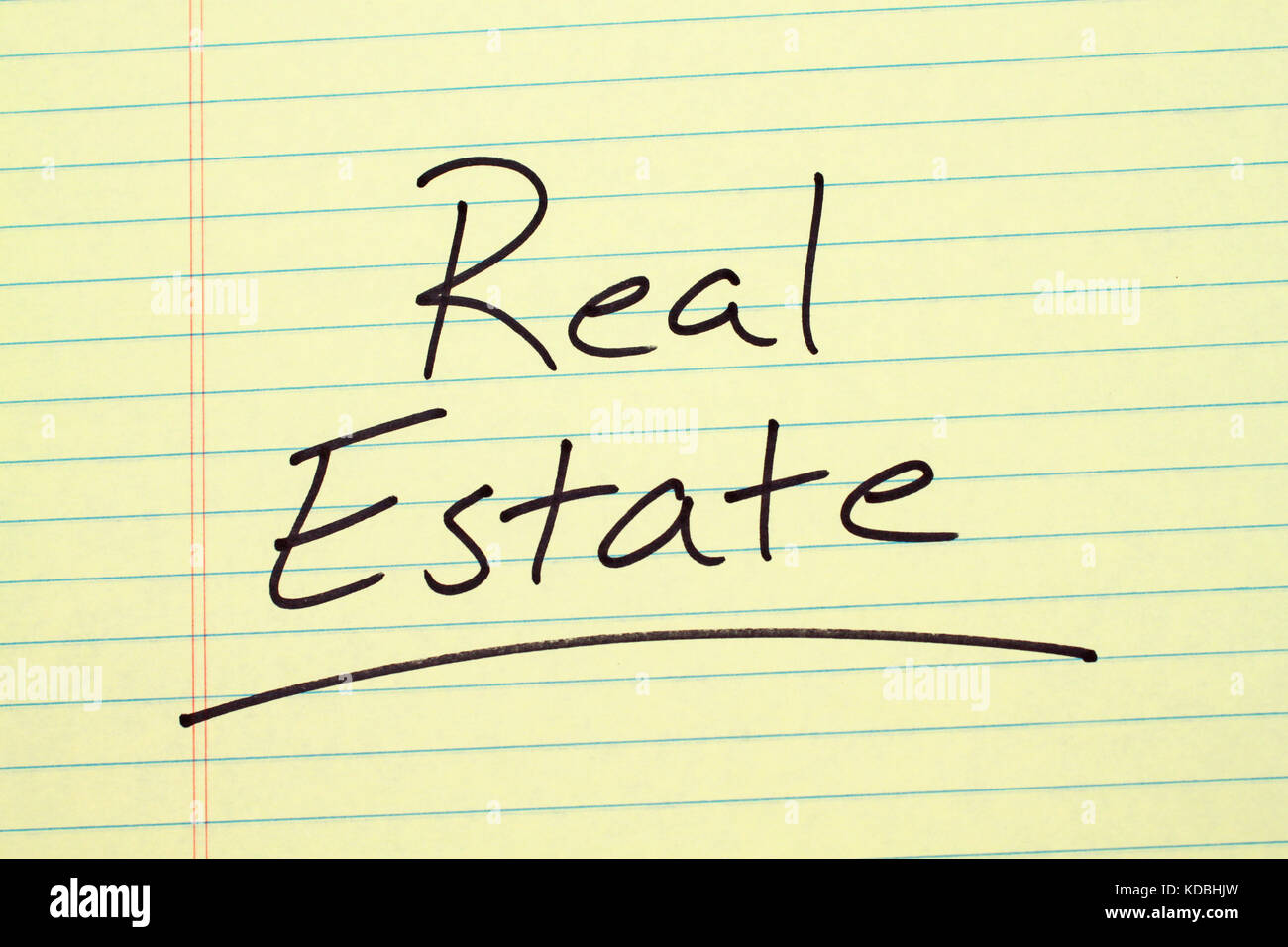 The word 'Real Estate' underlined on a yellow legal pad - Stock Image