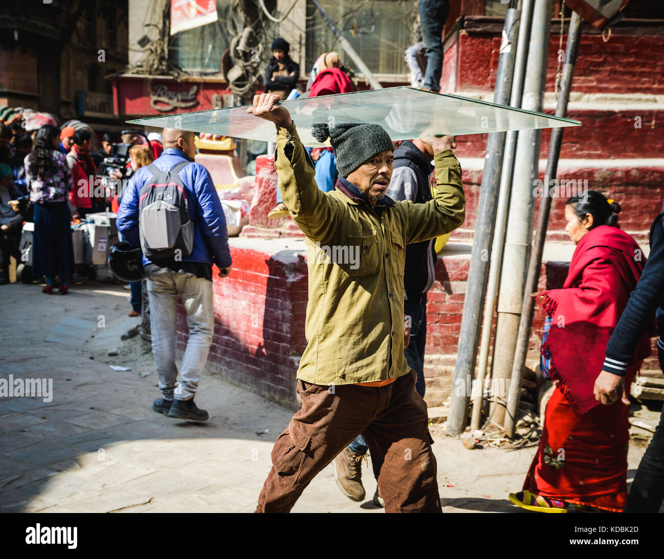 KATHMANDU, NEPAL - CIRCA JANUARY 2017: Nepali man carrying a sheet of glass on his head in Asan neighbourhood. - Stock Image
