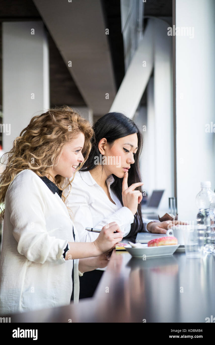 Two female workers in a design studio setting, working together. Caucasian and asian ethnicities. - Stock Image