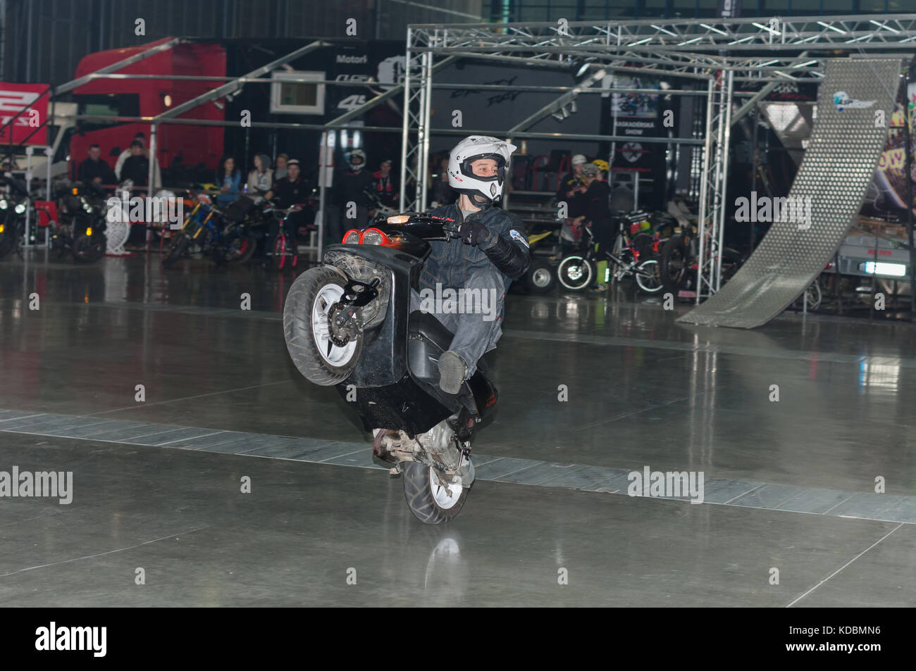 BRNO, CZECH REPUBLIC-MARCH 4,2016: Stuntman riding a scooter during stunt show on International Fair for Motorcycles - Stock Image