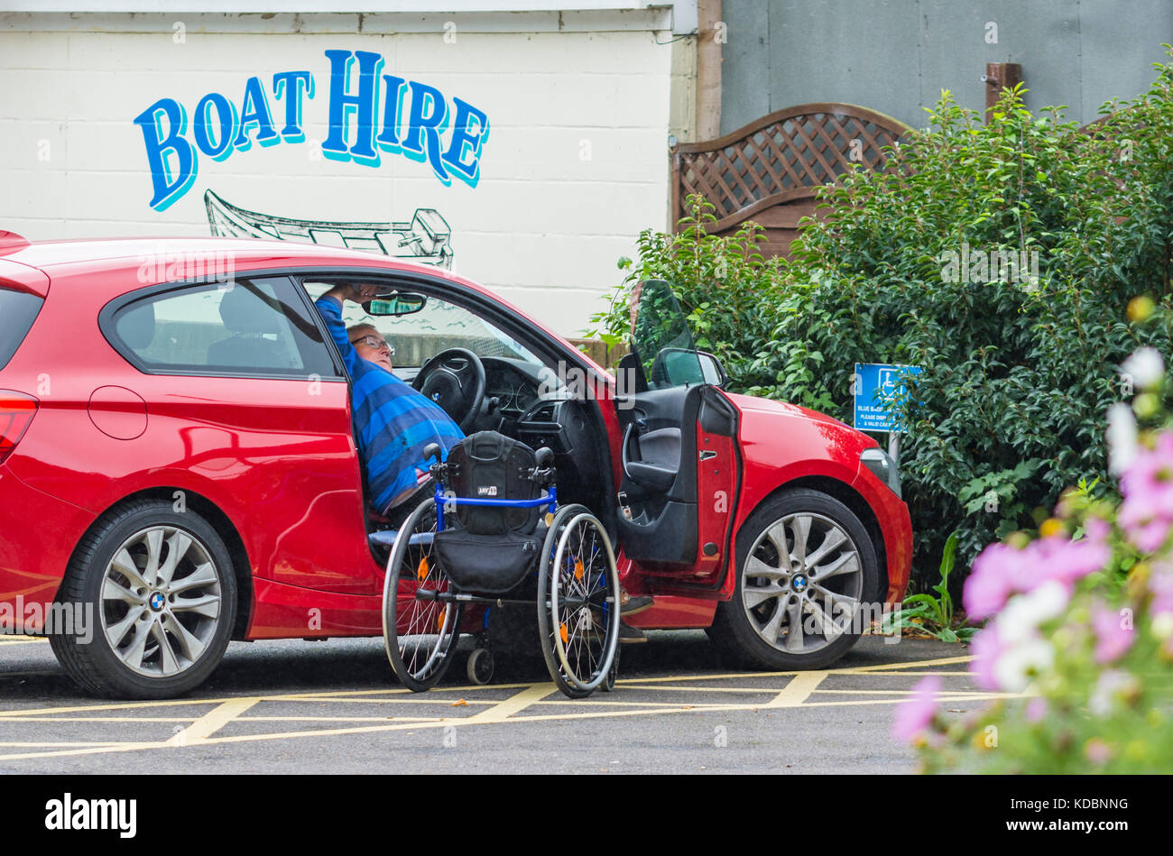 Disabled man climbing into a car from a wheelchair. - Stock Image