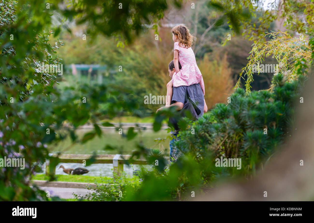 Young girl being carried on a man's shoulders, a piggy back ride, through a park in the UK. - Stock Image