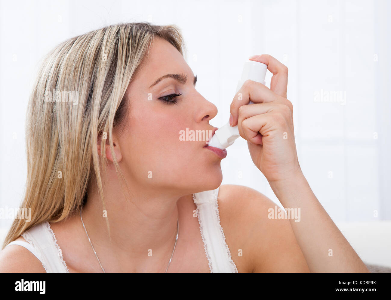 Woman with asthma using an asthma inhaler for preventing attacks - Stock Image