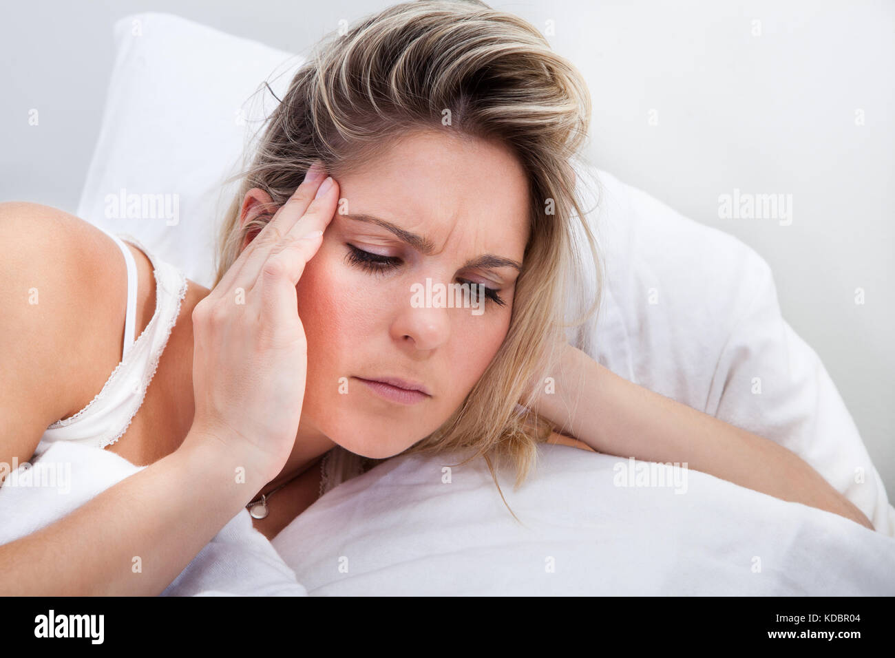 Portrait of woman with headache lying on bed - Stock Image